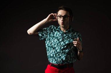 shocked fashionable man in eyeglasses listening music in headphones isolated on black