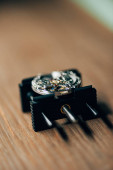 Selective focus of open wristwatch on movement holder on table