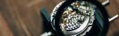Selektivní zaměření lupy a otevřených hodinek na stole, panoramatický záběr