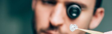 Selective focus of watchmaker holding watch part with tweezers, panoramic shot stock vector