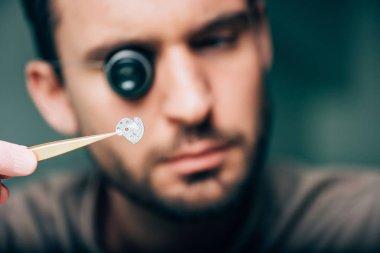 Selective focus of watchmaker holding watch part in tweezers stock vector
