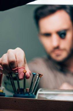 Masada çalışırken tornavida alan lateks parmak uçlu saat yapımcısının seçici odağı