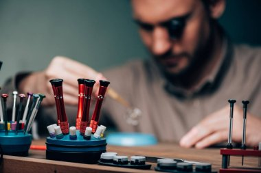 Selective focus of screwdrivers and equipment with working watchmaker at table