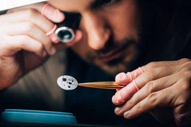 Selective focus of watchmaker holding eyeglass loupe and watch part in tweezers stock vector