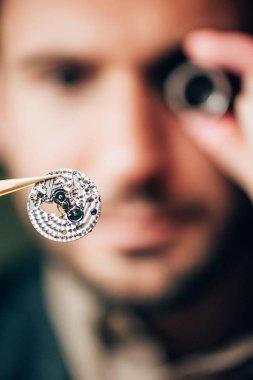 Selective focus of watchmaker holding part of mechanical wristwatch in tweezers stock vector