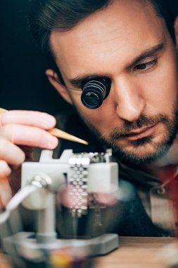 Selective focus of handsome clockmaker working with wristwatch on movement holder isolated on black