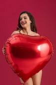 sexy dívka usmívá se zavřenýma očima, zatímco drží velké srdce ve tvaru balónu izolované na červené