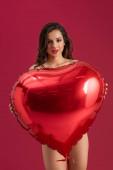 sexy dívka usmívá na kameru, zatímco drží velké srdce ve tvaru balónu izolované na červené