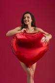svůdná dívka se usmívá a dívá se stranou, zatímco drží velký balón ve tvaru srdce izolovaný na červené