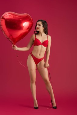 passionate girl in lingerie and high heeled shoes holding heart-shaped balloon while standing on red background