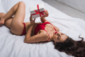 high angle view of seductive girl in red lingerie lying in bed and holding white gift box
