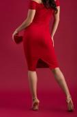 zadní pohled na svůdnou, elegantní dívku držící srdce ve tvaru dárkové krabice na červeném pozadí