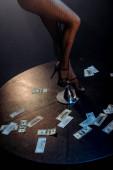 Ausgeschnittene Ansicht von sexy Stripperin in Strumpfhosen Pole Dance in der Nähe von Dollarnoten auf Schwarz