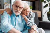 Selektivní zaměření staršího muže při pohledu na kameru podle manželky na gauči