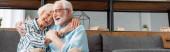 Panoráma lövés mosolygós idős nő ölelés férj kanapén otthon