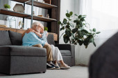Seitenansicht eines älteren Paares, das sich auf der Couch im Wohnzimmer umarmt