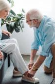 Boční pohled na starší muž tkaničky boty manželky na gauči doma