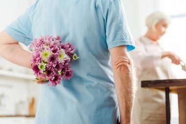 Selective focus of man hiding bouquet with wife by kitchen table at background
