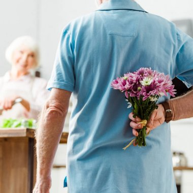 Selective focus of senior man hiding bouquet while smiling wife cooking at background