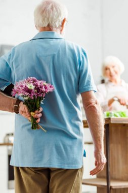 Selective focus of senior man hiding floral bouquet while smiling wife cooking in kitchen