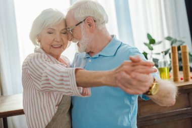 Selective focus of senior couple dancing in kitchen