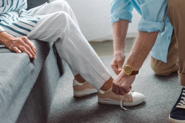 Cropped view of senior man lacing shoe of woman on couch