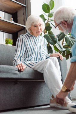 Selective focus of senior woman looking at husband lacing shoe in living room