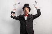 překvapený kouzelník házet hrací karty, na šedé