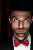 pohledný kouzelník v obleku, motýlek a klobouk v cirkuse s červenými závěsy