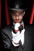 fiatal bűvész kezében mágikus labda cirkuszban vörös függönyök