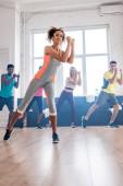 Szelektív fókusz afro-amerikai tréner gyakorló zumba multietnikus táncosok a tánc stúdióban