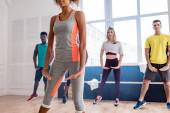 A többnemzetiségű zumba táncosok mozgását bemutató afro-amerikai tréner szelektív fókusza a táncstúdióban