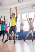 Az oktató és multikulturális táncosok szelektív fókusza, akik zumbát játszanak a táncstúdióban
