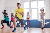Alacsony látószögű kilátás jóképű edző végző zumba többnemzetiségű táncosok a táncstúdióban