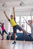 Alacsony szög kilátás többnemzetiségű táncosok kezét a levegőben gyakorló zumba a táncstúdióban