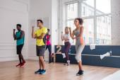 Smiling multicultural dancers performing zumba movements in dance studio