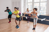 Multicultural zumba dancers training together in dance studio