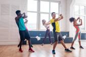 Fiatal multikulturális zumba táncosok mozgást gyakorolnak a táncstúdióban
