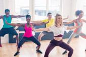 Szelektív fókusz mosolygó többnemzetiségű táncosok képzés zumba mozgalmak a táncstúdióban