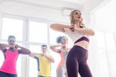 Alacsony látószögű kilátás fiatal multietnikus táncosok gyakorló zumba együtt tánc stúdió