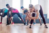 Alacsony szög kilátás az edző nyújtózkodó multietnikus zumba táncosok a stúdióban