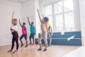 Tréner és többnemzetiségű táncosok kéz a levegőben gyakorló zumba a táncstúdióban