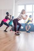 Alacsony szög kilátás többnemzetiségű zumba táncosok nyújtózkodó edzés közben tánc stúdió