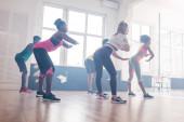 Seitenansicht junger multikultureller Tänzer, die Zumba-Bewegungen im Tanzstudio trainieren