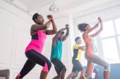 Alacsony látószögű kilátás afro-amerikai tréner tanulás multikulturális táncosok mozgása zumba a táncstúdióban
