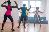 Zadní pohled multikulturních tanečníků vystupujících zumbu v tanečním studiu