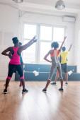 Vissza kilátás afro-amerikai zumba táncosok kezét a légi gyakorló mozgások stúdióban