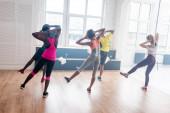 Back view of multiethnic dancers performing zumba movements in dance studio
