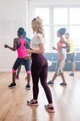 Oldalsó nézet többnemzetiségű táncosok gyakorló zumba együtt tánc stúdió
