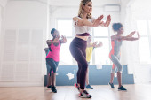 Mosolygó multikulturális táncosok, akik zumbamozgást végeznek a stúdióban